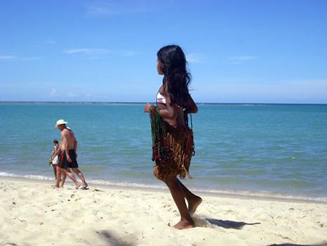 Niña pataxó vendiendo collares en la playa